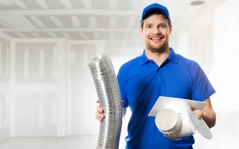 An HVAC technician holding up air duct parts.